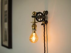 "Rusty Remakes Signature ""Fishy"". Small wall lamp designed from a vintage cast iron fishing reel pulley."