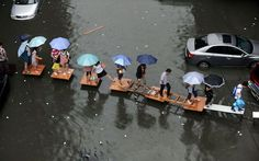 People hold umbrellas as they cross a flooded street by stepping on wooden tables and ladders amid heavy rainfalls in Wuhan, Hubei province, China. Sponge City, World Economic Forum, You Are The World, Save The Children, Greenhouse Gases, Wuhan, Extreme Weather, China Travel, Kids Health
