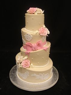 Peach and cream colored topsy-turvy wedding cake with pink ribbon and flowers.