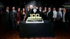 The cast and producers gathered around a massive cake.