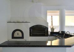 As bancadas em granito preto servem como apoio para a churrasqueira ou o forno a lenha no preparo das refeições servidas ao ar livre.