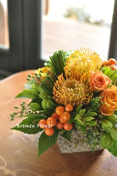 Yellow pincushion proteas, orange roses, green leucadendrons
