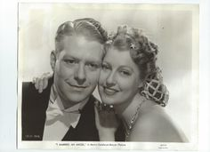 """Original, vintage photo of Jeanette MacDonald and Nelson Eddy dated July 1, 1942. Back of the photo says: """"Nelson Eddy's mind is full of confusion when he dreams that Jeanette MacDonald, quiet secretary is an angel and that he marries her.Being married to a heavenly being might sound very nice, but they have an annoying manner of being much too truthful and Jeanette is no exception.  - ESCANO COLLECTION"""