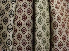 Jim Dickens -  Farnese Fabric Collection - Small blue, red, green and brown patterned ovals printed in rows over four fabricsin a beige colour