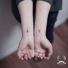 Matching key and keyhole tattoos on the wrist.