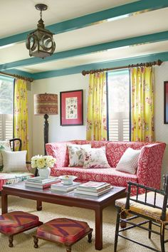 The vibrant turquoise on the trim and beams echoes the blue-greens in the entry's floral wallpaper. Many of the fabrics in the living room are from the new Madcap Cottage Into the Garden collection by Robert Allen @ Home.