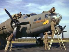 Flight and ground crews of a B-17 bomber make adjustments to their plane prior to a mission in England, fall 1942.