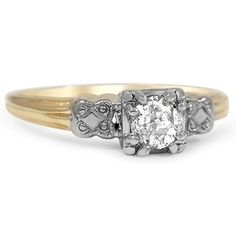 This lovely Retro engagement ring features a sparkling old mine cut diamond in a classic basket setting. Delicately sculpted white gold designs embellish the top of the shank, which is made of warm yellow gold (approx. 0.22 total carat weight).