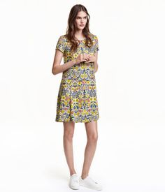 Light beige/floral. Short dress in woven fabric with a printed pattern. Opening and ties at back of neck, short sleeves, and gentle flare to hem. Unlined.