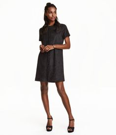 Short dress in imitation suede with a heavy drape. Braided section at front, short visible zip at back of neck, and short sleeves. Unlined.