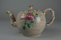 Teapot and cover; salt-glazed stoneware; enamelled; globular body with crabstock spout and handle; floral knop; spout and handle decorated with bark pattern in pink and black; body and cover covered with pink scale pattern and each with two flower sprays in pink, green, blue and yellow; knop with dabs of pink, greeb and yellow; base also scaled.