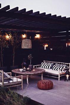 Coussins graphiques et pouf en cuir artisanal, mobilier en bois, dans un cadre en bois noirci pour plus de sophistication. Élégant et chaleureux.