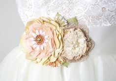 A beautiful addition to your country wedding dress! This colorful floral bridal sash is blooming with pink, light yellow, green, and ivory white handmade fabric and lace flowers. The vintage enamel fl
