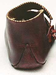 "The top of the shoe is ""whipped"" with a contrasting color thread, both as decoration and to reinforce the edge (right). The sole extends well up the back of the heel, perhaps to provide some additional life to the shoes by keeping the heel seam up off the ground where it can't be scuffed."
