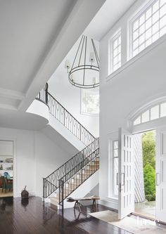 A white, open entryway adds a touch of classic elegance to this Hamptons home. A staircase with a custom iron railing leads up to the second floor.