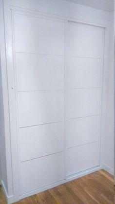 Frente de armario con puertas correderas blancas con franjas horizontales con fresado en V.