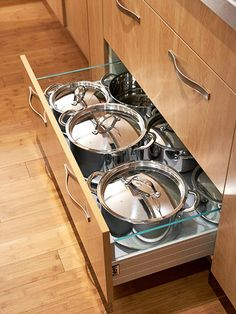 4 of 28   Smooth Operations  Deep drawers under the cooktop are designed to accommodate large pots with their lids in place. The drawer glides open easily, even when fully loaded. Glass panels on the sides make it easy to see what's inside. The drawer fronts look like solid wood, but they are actually laminate