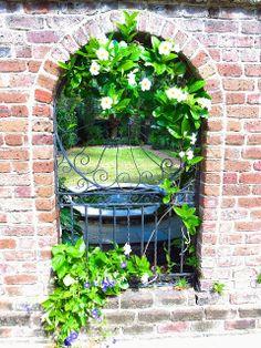 """Brick arch and wrought iron garden gate window in Charleston, South Carolina"""