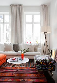 Step inside this beautiful Stockholm home  where the layers of colour and pattern found in the rugs and artwork soften the clean Scandinavia...