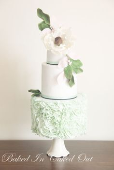 Mint and white wedding cake with a giant sugar magnolia with berries and leaves. Ruffles on bottom tiers are inspired by Vera Wang a technique used by many sugar artist.