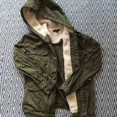 Military style coat with cozy detail Green military style coat with faux wool lined hood and around interior. This coat is not fully lined - just around the edge to appear lined while wearing. It is not a warm jacket. Fits true to size. Extra button still attached. Never worn. Mine Jackets & Coats