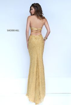 Luscious novelty jersey brings sensual sheen to the Sherri Hill 50017 full-length prom dress. This halter neck jersey gown showcases a tapered bodice edged with metallic bands. It features curvaceous side cutouts and an inverted waistline. A single strap crosses the open back above the midriff encircling waistband. The long skirt boasts a daring high-thigh center front slit and an inset sweep train.