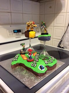 3D Super Smash Bros cake! Mushroom land board adapted into an 18 for his eighteenth birthday. Surprised him with the Bowser amiibo! Cutting out the holes in the 8 was pretty easy with a knife but covering them in icing was quite tough. Taped amiibos to wax paper to protect the bases while they sat on the cake.