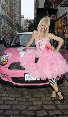 Betsey Johnson in pink poses on her streched pink mini cooper.