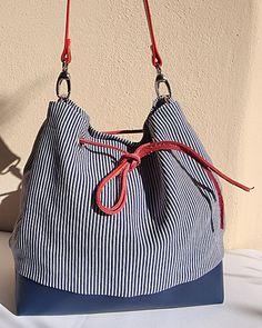 Grande borsa secchiello in tela a righine bianche e blu con fondo in similpelle blu e tracolla in vera pelle rossa di ottima qualità. Si chiude con un laccio in vera pelle rosso. La fodera è in raso blu.Internamente ci sono 5 tasche delle quali una con cerniera.