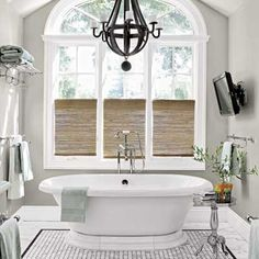 Scale, proportion, and style mix it up in the master bath. The vintage-look train rack and tub filler mingle with a flat-screen TV and an oversize iron-and-wood chandelier that was nabbed at a flea market and looks as if it migrated from the dining room. |  Tub: @kohlerco | Filler: @perrinandrowe | Towel racks: Restoration Hardware