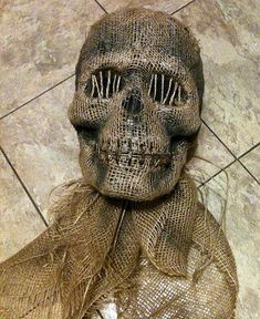 DIY creepy Halloween skull - cheap plastic or foam skull + burlap glued over it + staples and twine across mouth + twine over eye sockets + paint to make it look grungy - genius! This link is to 2nd page in this post - go to 1st page to see some basic steps - this is more of a general how-to than a detailed tutorial