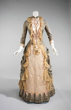 This is an American-made dress for a 50th wedding anniversary.  The style evokes 18th century and would have been appreciated for its beautiful embroidery and lace trim. <br/><br/>The bustle silhouette, although primarily associated with the second half of the 19th century, originated in earlier fashions as a simple bump at the back of the dress, such as with late 17th-early 18th century mantuas and late 18th- early 19th century Empire dresses