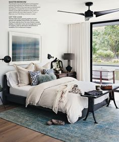 overdyed rug, layered bedding, comfy bedroom, white walls, modern ceiling fan, lots of pillows, art over bed, bedside sconces