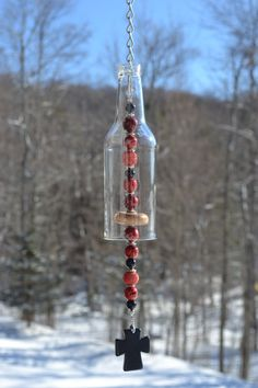 This wind chime is a smaller version of my wine bottle wind chimes.I made this from a clear bottle. I cut the glass myself and sanded the edges. It hangs from silver rings and chain. It has red, black and silver beads and a wooden knocker. It also has a black cross for a pendulum.