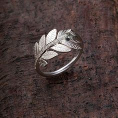 This is a beautiful leaves engagement ring, made of silver and a line of shiny cubic zirconia stones
