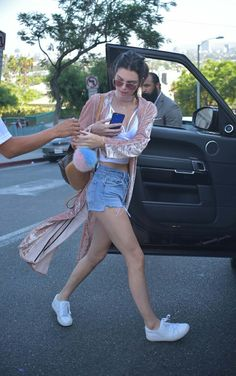 Kendall Jenner in a blush velvet robe, denim cut-offs, Ray-Ban sunglasses, Louis Vuitton bag, white Kenneth Cole shoes.
