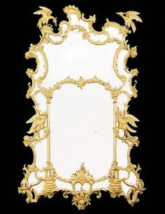 Giltwood Mirror. The shaped divided plates are within a leaf-wrapped and rockwork-carved frame centred by a C-scroll cresting and an apron. The apron is centred by confronting C-scrolls issuing a cabochon and rockwork, the lower plate flanked by Gothic cluster columns. English, Nineteenth Century