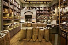 The burlap sacs and lights really make this store seem so cute and rustic Supermarket Design, Retail Store Design, Retail Shop, Bulk Store, Grocery Store, Chocolate Stores, Chocolate Store Design, Herb Shop, Spice Shop