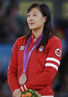 Bronze medalist Carol Huynh of Canada, participates in the awards ceremony for 48-kg women's freestyle wrestling at the 2012 Summer Olympics, Wednesday, Aug. 8, 2012, in London.