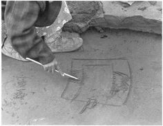 A girl uses a story knife for drawing pictures in the ground to illustrate a story. Bethel, 1936.