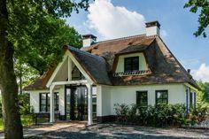 Wat direct opvalt aan deze rietgedekte villa te laren is de imposante entree: dubbele voordeur, zij- en bovenlichten en een heuse overkapping.
