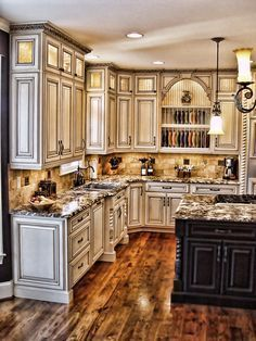 Absolutely love the wood floors here; and the distressed appearance & color of cabinets. with the dark island cabinets. :)