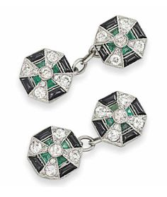 A PAIR OF EARLY 20TH CENTURY DIAMOND & GEM CUFFLINKS   Each panel of octagonal form, the central millegrain-set old-cut diamond cross motif interspersed with emerald accents, to the buff-top onyx border, with chain link connections between, ca 1915.