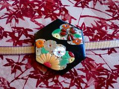 Obidome are small brooches worn threaded onto the obijime (a decorated sash in order to tie an obi firmly), not really necessary, but making a charming decoration on the front of the obi.