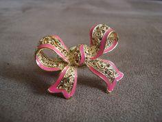 Anel em metal dourado em formato de laço com partes esmaltadas em rosa neon.  Aro 18 (diâmetro: 1,75cm) R$29,90