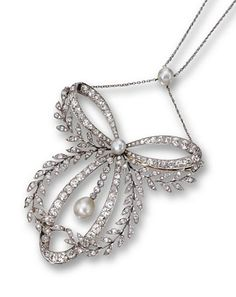 DIAMOND AND PEARL PENDANT-BROOCH/NECKLACE.  The ribbon bow entwined with a foliate garland, set with 271 old European-cut diamonds weighing approximately 11.25 carats and 6 old European-cut diamonds weighing approximately .35 carat, the center accented with a button pearl and supporting a fringe anchored by a pearl drop measuring approximately 10.3 by 8.8 mm., suspended from a chain accented with a button pearl of approximately 8.0 mm., length 18 inches, chain and brooch fitting detachable.