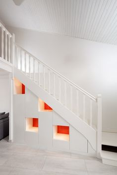 Placards sur-mesure sous-escalier, mélaminé blanc et niches à fond rouge