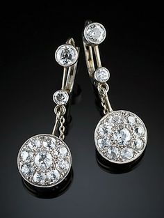 Art Deco diamond cluster pendant earrings  Art Deco diamond, platinum and gold cluster pendant earrings with fine safety chains. Circa 1920s.