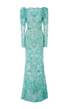 This **Elie Saab** dress features a rounded neckline, allover intricate beaded detail, and juliet style sleeves.