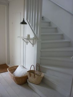 crisp white on walls and stairs, small shelf and down light...beautiful with so little.